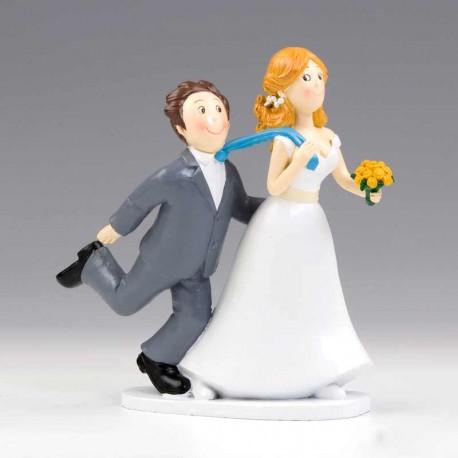 Divertida figura de novios con la novia arrastrando al novio de la corbata