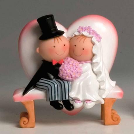 Pit y Pita novios sentados en un banco con forma de corazón, figura para tartas de boda
