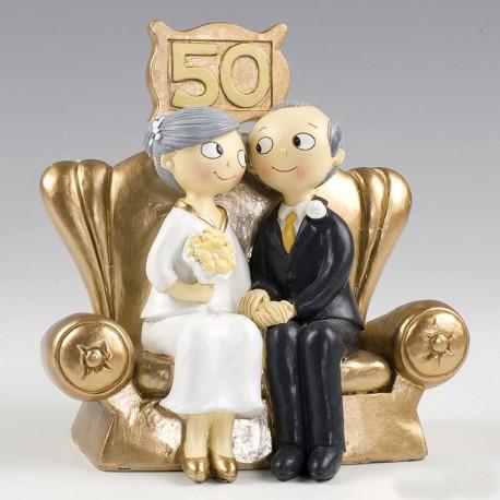Simpática pareja sentada en un trono dorado, figura para celebrar las bodas de oro