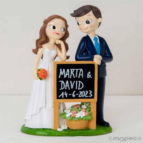 Figura para tarta de novios con pizarra, con el nombre de los novios y fecha de la boda